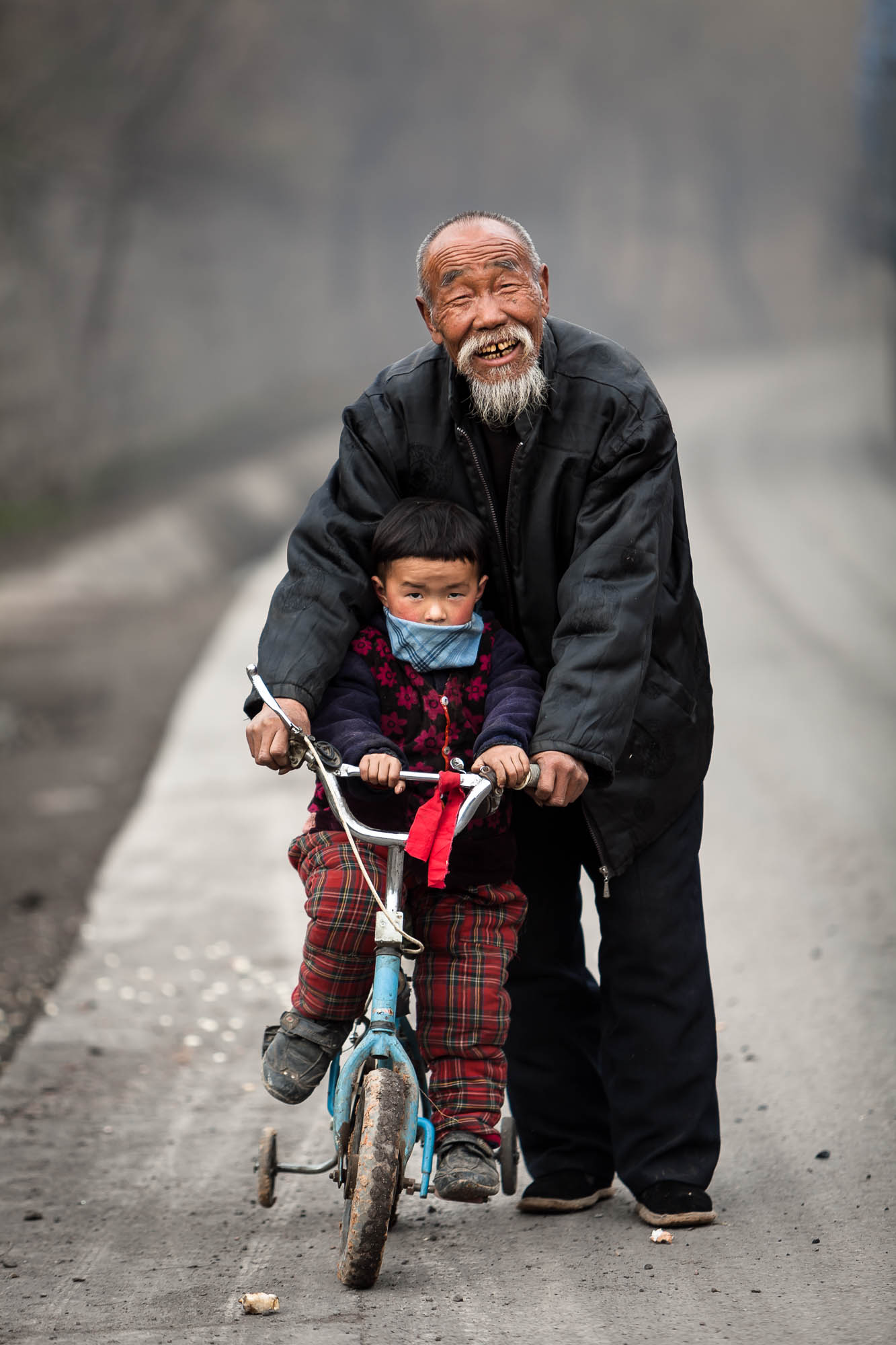 Out on the country road, with training wheels and grandpa.