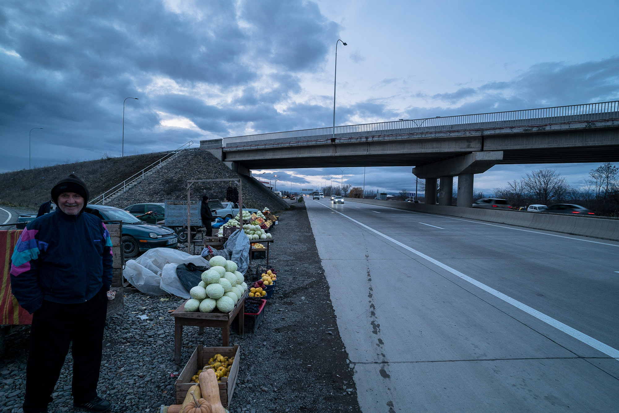 people selling fruits next to the highway