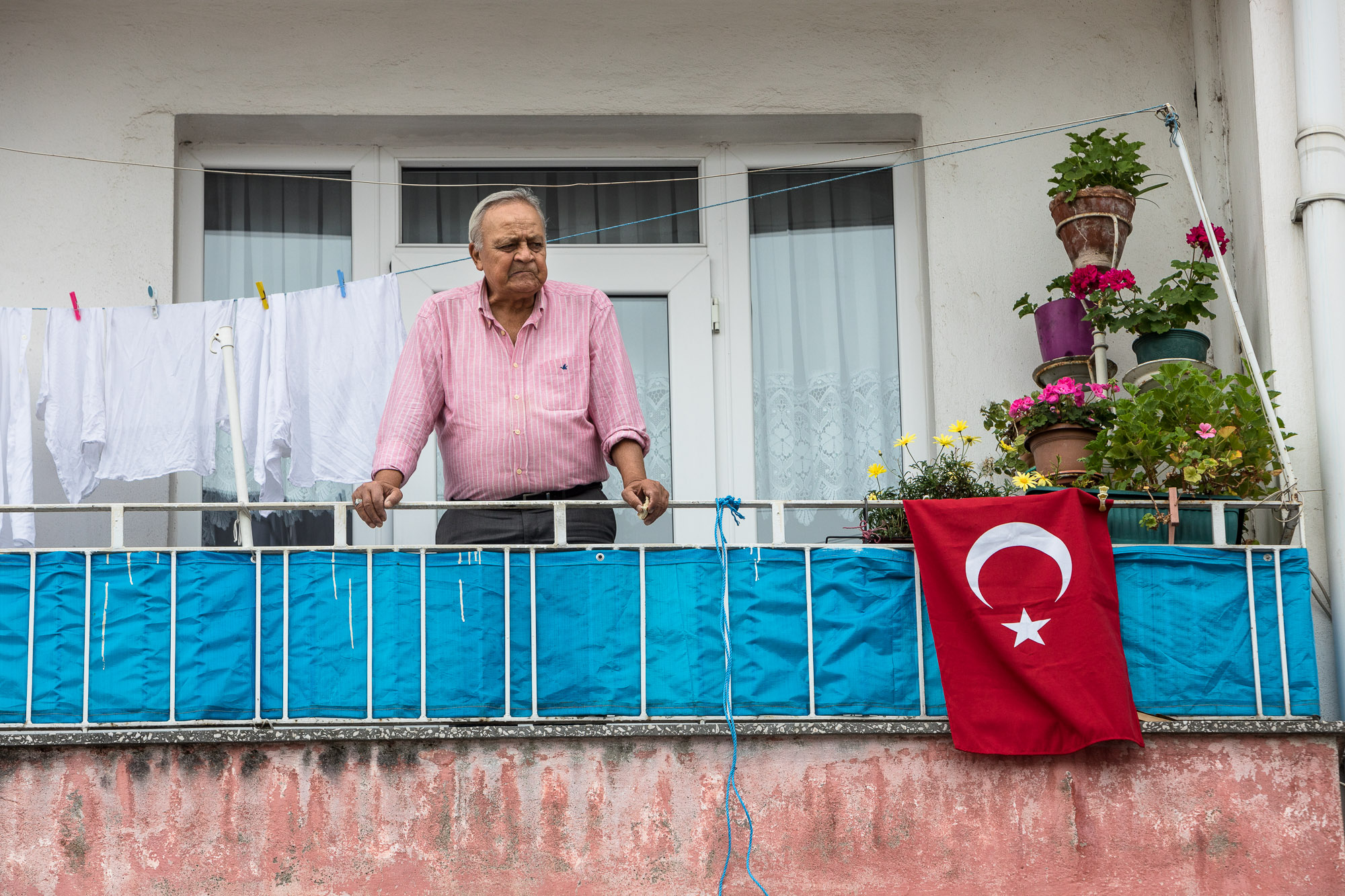 man with Turkish flag on balcony